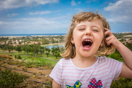 loudly: Little girl standing on a viewpoint over Maspalomas in gran Canaria and shouting loudly Stock Photo