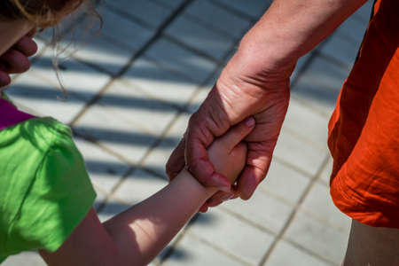 Grandmother and granddaughter holding hands together during a walk in town Standard-Bild