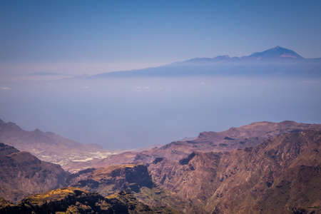 visible: Panoramic view from the plateau from Roque Nublo with Tenerife and Mount Teide  its highest peak visible in the distant background