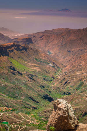 visible: View from the plateau from Roque Nublo with Tenerife and Mount Teide  its highest peak visible in the distant background Stock Photo