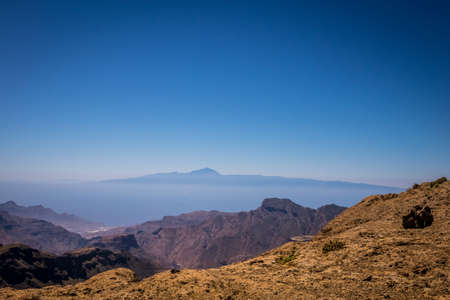 tableau: Panoramic view from the plateau from Roque Nublo with Tenerife and Mount Teide  its highest peak visible in the distant background