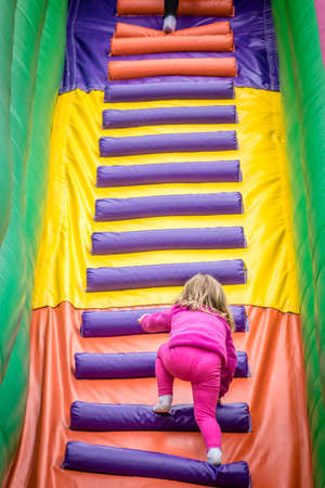 playcentre: Little girl climbing up the stairs to the top of an inflatable mega slide in an outdoor funfair playground Stock Photo