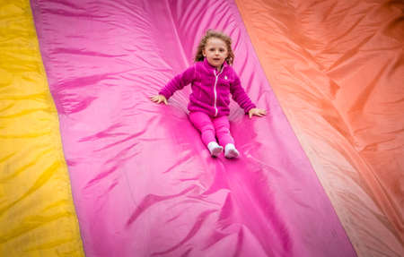 captivated: Little girl sliding down on a big inflatable mega slide in an outdoor funfair playground