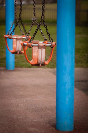Two empty swings in an outdoor playground photo