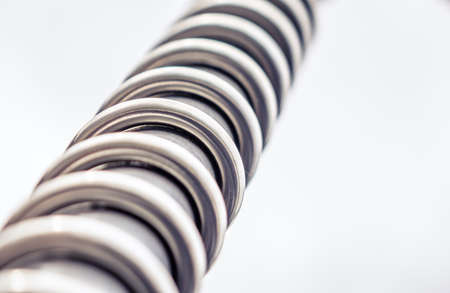 twisting: Close up of a twisting metal spiral over white background