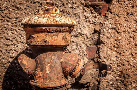 waste prevention: Disused and rusted old hydrant in front of a old home Stock Photo