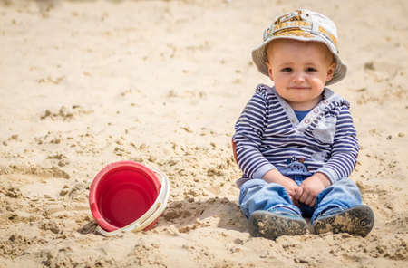 sandpit: Cute little boy sitting in a sandpit in an outdoor playground
