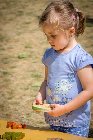 educational problem solving: Little girl playing with the wooden puzzle in the playground