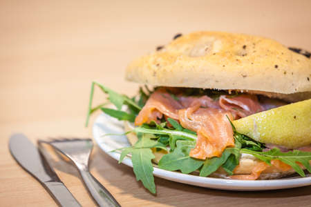 filled: Breakfast bun on a plate, filled with smoked salmon and rocket salad