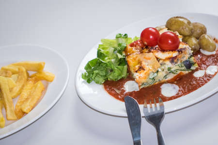 vegetable tin: Feta and spinach layered quiche served with tomato sauce, cherry tomatoes and roast potatoes