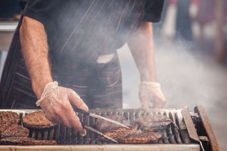 Chef  preparing burgers at the barbecue outdoors