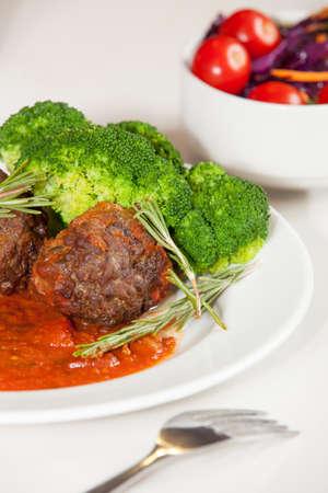 side salad: Meatballs with tomato sauce served with broccoli and side salad