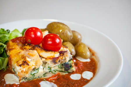 roast potatoes: Feta and spinach layered quiche served with tomato sauce, cherry tomatoes and roast potatoes