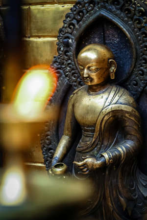 deity: Brass figurine of a deity and candles burning inside one of the Buddhist temples in Nepal