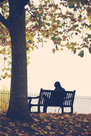 bench alone: Man sitting alone on the bench on a cloudy, rainy autumn day