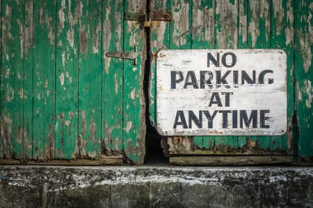 stating: Sign attached to the old green wooden gates of a barrack stating that parking is not allowed at anytime