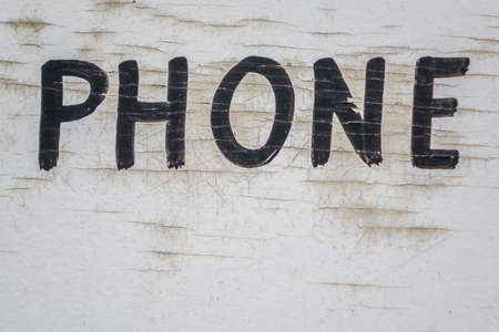and spelling: Letter spelling phone written on an old weathered wooden white wall