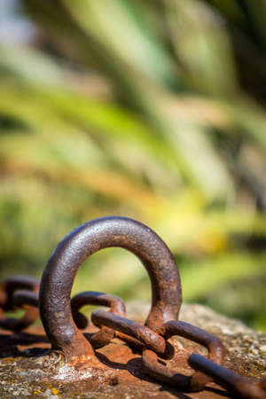 joining forces: Old rusted chain attached to the stone wall in the port