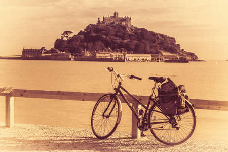 leaned: Bicycle leaned on a wooden barrier on a promenade on a coast of Marazion with the St Michaels Mount in the background, Cornwall, England