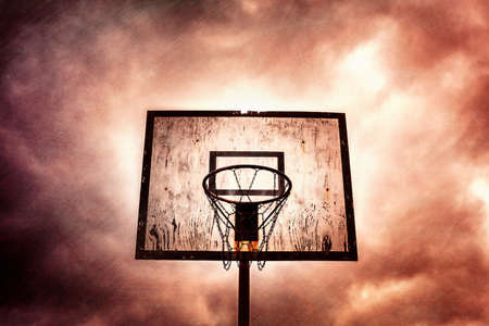 disused: Old disused outdoor basketball hoop on a stormy, cloudy day