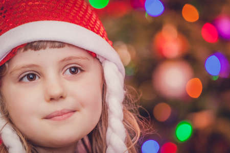 mesmerized: Cute Christmas girl with the Christmas tree lights bokeh in the background