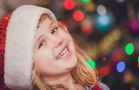 niños riendose: Cute Christmas girl with the Christmas tree lights bokeh in the background