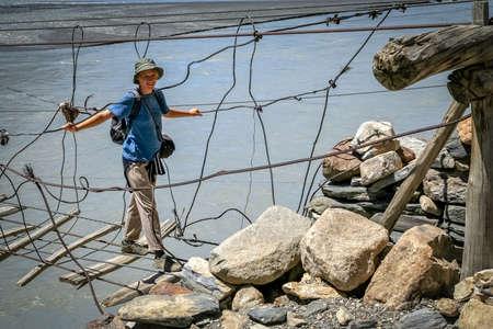 perilous: Woman traveller crossing the unstable bridge across Hunza river in Karakorum