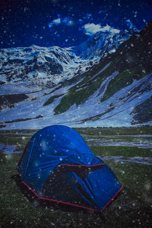 pitched: Tent pitched on a meadow at Nanga Parbat base camp at night during snowfall