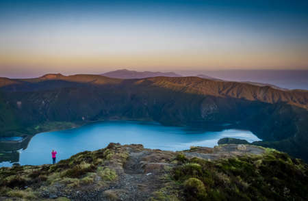 stunningly: Woman traveller standing on the rim and taking pictures of the stunningly beautiful volcanic crater lake Lagoa do Fogo ( Fire Lake ), Sao Miguel, Azores, Portugal.