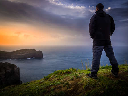 admiring: Traveller standing on the top of a cliff and admiring the sunset, Sao Miguel Island in the Azores, Portugal Stock Photo