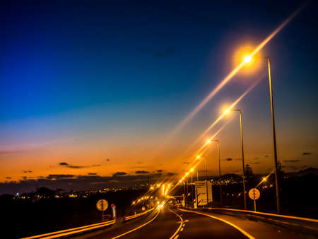 approaching: Motorway leading to the town of Ponta Delgada in sao Miguel, Azores, Portugal, with lampposts lit at dusk