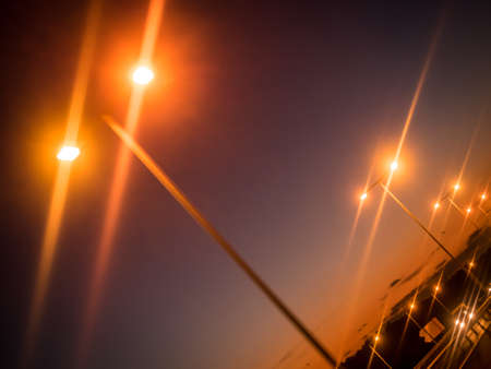 leading light: Lampposts lit at dusk on the motorway leading towards the city Stock Photo