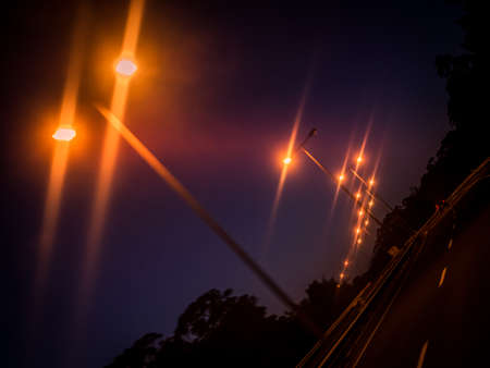 towards: Lampposts lit at dusk on the motorway leading towards the city Stock Photo
