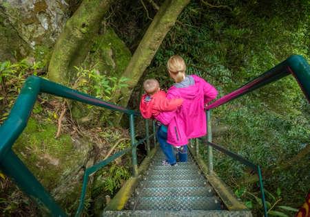 bajando escaleras: Madre que lleva a su hijo al ir escaleras empinadas que conducen a la parte superior de la cascada de dos niveles en una garganta, Isla de Sao Miguel, Azores, Portugal Foto de archivo