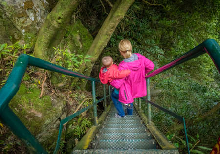 tier: Mother carrying her son while going down steep stairs which lead to the top of the two tier waterfall in a gorge,  Sao Miguel Island, Azores, Portugal Stock Photo