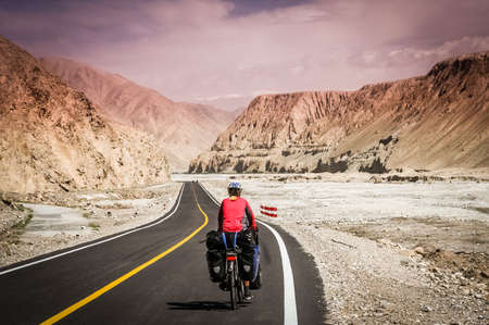 stunning: Woman cyclist on stunning KKH road through Karakorum mountains in southern China