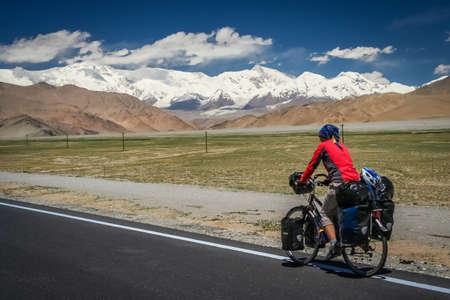 touring: Woman cyclist on stunning KKH road through Karakorum mountains in southern China