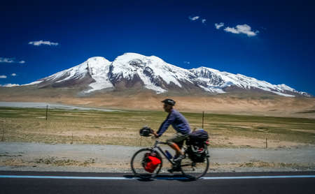ata: Single male cyclist on the bicycle cycling in front of the Muztagh Ata peak on the Karakorum Highway in China
