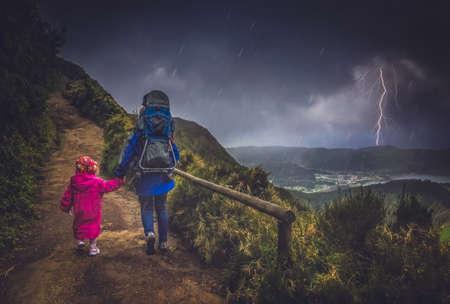 niños caminando: La madre y sus hijos caminando en un sendero de montaña en tormenta y el tiempo lluvioso, Sao Miguel, Azores, Portugal Foto de archivo
