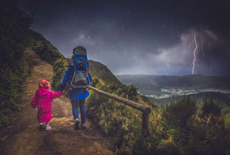 girl in rain: Mother and her children walking on a mountain trail in stormy and rainy weather, Sao Miguel, Azores, Portugal Stock Photo