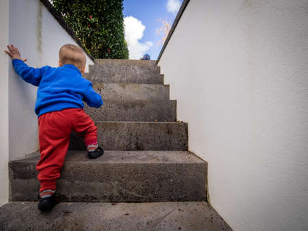 upstairs: Cute baby boy climbing up the stairs Stock Photo