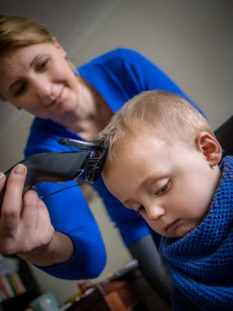 cutting hair: Mother cutting hair of her little son Stock Photo