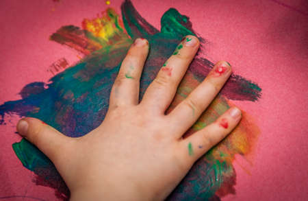attentive: Child hand making colorful marks on a paper with a watercolor paint
