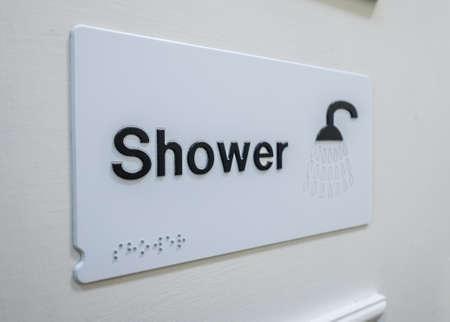 washroom: Shower sign on a door of a washroom in a hotel