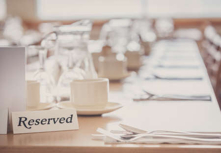 booked: Wine glasses, coffee cups and cutlery on the table reserved by customers before the start of the service in the restaurant