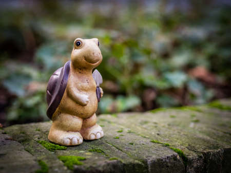 garden statuary: Small turtle figurine standing on a wall in the garden
