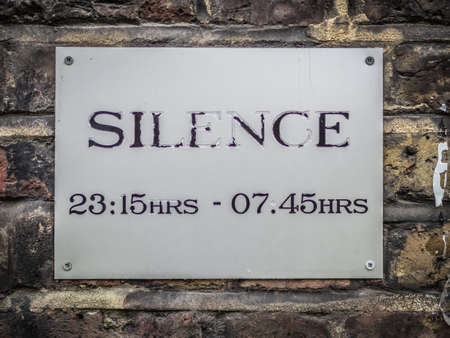 premises: Wall plaque indicating the there has to be silence on the premises between eleven fifteen pm and seven forty five am