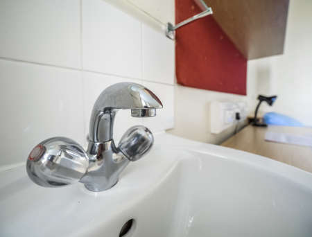 washroom: Silver chrome hot and cold water tap on a sink in a home washroom