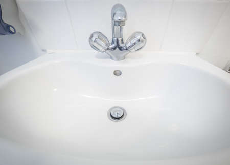 Silver chrome hot and cold water tap on a sink in a home washroom