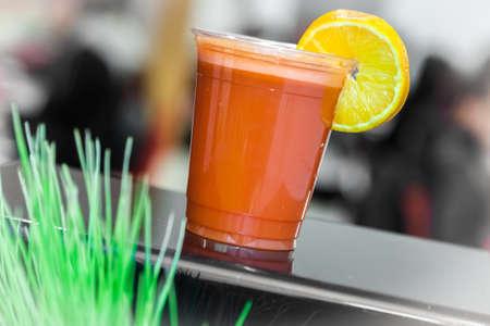 reciclable: batido de naranja y zanahoria en una taza de plástico reciclable con una paja Foto de archivo